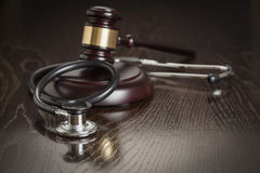Judge's Gavel and Stethoscope on Reflective Table Royalty Free Stock Images