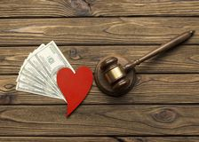 A judge`s hammer, American dollar bills. A heart shape on a wooden background. family law Royalty Free Stock Images