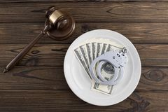Judge`s hammer, dollar bills, handcuffs in a dinner plate on a wooden background. Bribe. arrest. law violation Stock Photos