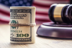 Judge`s hammer gavel. Justice dollars banknotes and usa flag in the background. Court gavel and rolled banknotes. stock photo