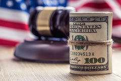 Judge`s hammer gavel. Justice dollars banknotes and usa flag in the background. Court gavel and rolled banknotes. Stock Images