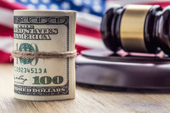 Judge`s hammer gavel. Justice dollars banknotes and usa flag in the background. Court gavel and rolled banknotes. Still life of a bribery, corruption in the US royalty free stock image