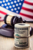 Judge`s hammer gavel. Justice dollars banknotes and usa flag in the background. Court gavel and rolled banknotes. royalty free stock photos