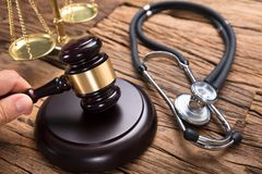 Judge`s Hand Hitting Mallet By Stethoscope And Justice Scale. Judge hitting mallet by stethoscope and justice scale on wooden table in courtroom royalty free stock images