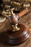 Block gavel and wig. Judge's wig and his gavel on wooden block stock image