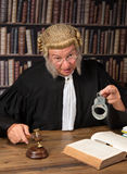 Judge showing handcuffs. Old judge with authentic wig in courtroom holding handcuffs royalty free stock photo