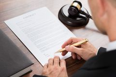 Judge signing contract paper at desk Stock Images