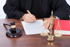 Judge signing contract paper at desk. Midsection of male judge signing contract paper at desk Royalty Free Stock Image