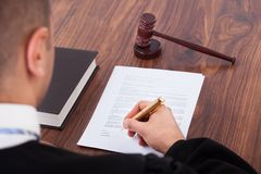 Judge signing document in courtroom. Cropped image of judge signing document in courtroom Royalty Free Stock Photography