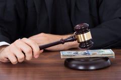 Judge striking gavel on banknotes at desk Stock Photo