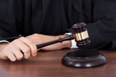 Judge striking gavel on block at desk. Midsection of male judge striking gavel on block at desk in courtroom Royalty Free Stock Photos