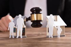 Judge Striking Gavel Between Split House. Judge Striking Gavel Between Family Figure Cut Out And Split House Over Wooden Desk royalty free stock photography