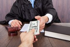 Judge taking bribe from client. Midsection of judge taking bribe from client at desk in courtroom Royalty Free Stock Photo