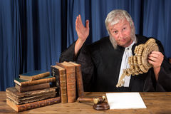 Judge taking wig off. Mature judge taking his wig off in court stock image