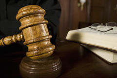 Judge Using Gavel. Closeup of judge using wooden gavel in courtroom Royalty Free Stock Photo