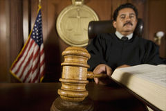 Judge Using Gavel In Court. Portrait of a male judge knocking gavel in the courtroom Royalty Free Stock Photos