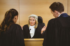 Judge wearing a dress and a wig speaking with lawyers Stock Photo