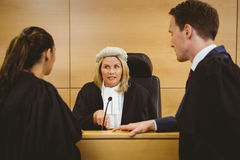 Judge wearing a dress and a wig speaking with lawyers Stock Photography