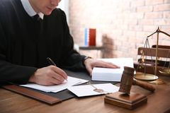 Judge working with papers and gavel on table, closeup. Law and justice royalty free stock photo