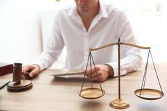 Judge working at table in courtroom, focus on scales royalty free stock photos