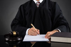 Judge Writing On Paper In Courtroom Stock Photography