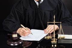 Judge writing on paper at desk Stock Photography