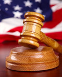 Judges gavel with flag. Judges wooden gavel with USA flag in the background Royalty Free Stock Image