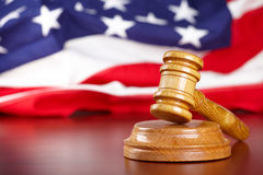 Judges gavel with flag. Judges wooden gavel with USA flag in the background stock photo