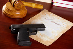 Judges gavel with gun and very old paper. Judges wooden gavel with gun and very old paper with word law in the background - horizontal stock photo