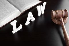 Judges Gavel, Red Book And Sign LAW On Black Table. Judges Gavel, Red Open Legal Book And White Sign LAW From Wood Latter On The Black Table In The Back Light Stock Photo