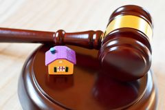 Judges gavel on sound block next to yellow colorful house stock image