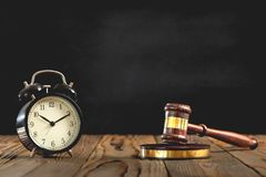 Judges Hammer with Alarm Clock on Black Board Background, Justice Concept royalty free stock photo