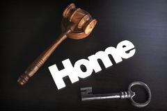 Judges Hammer or Gavel With Home Sign On Dark Background. Auctioneers or Judges Hammer or Gavel with White Home or House Sign On Black Wooden Background, Trial stock photo