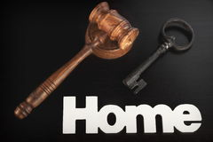 Judges Hammer or Gavel With Home Sign On Dark Background. Auctioneers or Judges Hammer or Gavel with White Home or House Sign On Black Wooden Background, Trial royalty free stock image
