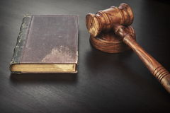 Judges Hammer or Gavel With Old Book On Dark Background. Auctioneers or Judges Hammer or Gavel with Old Book On Black Wooden Background Auction Or Trial Or Law stock photography