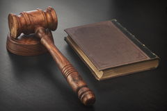 Judges Hammer or Gavel With Old Book On Dark Background. Auctioneers or Judges Hammer or Gavel with Old Book On Black Wooden Background Auction Or Trial Or Law royalty free stock images