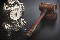 Judges Hammer or Gavel With Old Clock On Dark Background. Auctioneers or Judges Hammer or Gavel with Old Silver Clock On Black Wooden Background, Time For Trial royalty free stock images