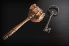 Judges Hammer or Gavel With Old Key On Dark Background. Auctioneers or Judges Hammer or Gavel with Old Key On Black Wooden Background, Trial Or Auction Concept royalty free stock images