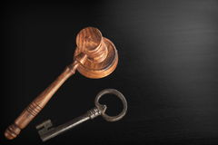 Judges Hammer or Gavel With Old Key On Dark Background. Auctioneers or Judges Hammer or Gavel with Old Key On Black Wooden Background, Trial Or Auction Concept royalty free stock image