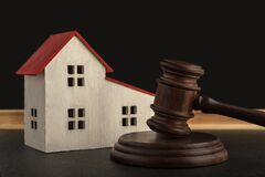 Judges hammer and model of house. Confiscated housing. Resolving property disputes