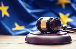 Judges wooden gavel with EU flag in the background. Symbol for jurisdiction Stock Image