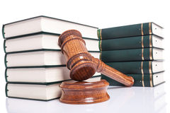 Judges wooden gavel leaning against law books. On white background royalty free stock image