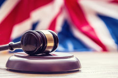 Judges wooden gavel with UK flag in the background. Symbol for jurisdiction Royalty Free Stock Image