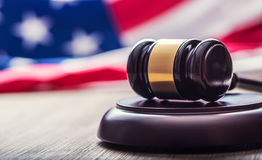 Judges wooden gavel with USA flag in the background. Symbol for jurisdiction Stock Images