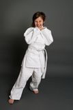Judo. Little girl in judo clothing against grey background royalty free stock images
