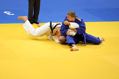 Judo action - submission technique. Philipp Galandi (in blue) from Germany performing a submission technique on Anton Savytskiy (in white) from Ukraine during stock images