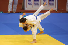 Judo action - throwing maneuver. Judo action: unknown judo fighters performing during the European Judo Championships for Individual Juniors held in Bucharest royalty free stock image