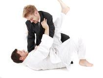 Judoist vs businessman. Judoist fight together with businessman Stock Images