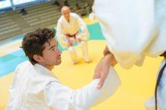 Judoka που ενισχύεται από το φίλο για να σταθεί επάνω μετά από την ήττα στοκ εικόνα