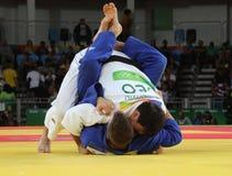 Judoka Beka Gviniashvili av Georgia i vit i handling mot Benjamin Fletcher av Storbritannien under match för män -100 kg Arkivbild